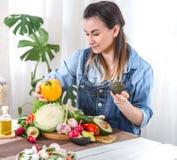 Νέα και ευτυχής γυναίκα που τρώει τη σαλάτα στον πίνακα στοκ φωτογραφίες