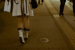 Νέα και μοντέρνα θηλυκά πόδια στα υψηλά παπούτσια τακουνιών που περπατούν γρήγορα σε έναν δρόμο με έντονη κίνηση τη νύχτα στοκ εικόνες