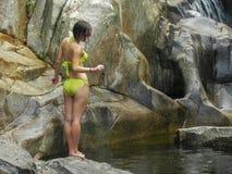 Νέα και προκλητική γυναίκα σε ένα πράσινο μαγιό σε έναν όμορφο καταρράκτη στοκ εικόνες