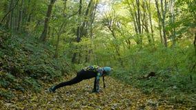 Νέα και υγιής άσκηση γιόγκας λήξης γυναικών στο δάσος απόθεμα βίντεο