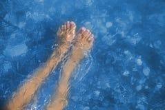 Νέα και όμορφα θηλυκά γυμνά πόδια με τα κόκκινα χρωματισμένα καρφιά που στέκονται σε μια παραλία κάτω από τα κύματα Στοκ φωτογραφία με δικαίωμα ελεύθερης χρήσης