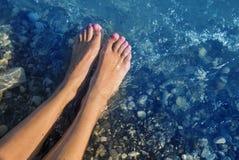 Νέα και όμορφα θηλυκά γυμνά πόδια με τα κόκκινα χρωματισμένα καρφιά που στέκονται σε μια παραλία κάτω από τα κύματα Στοκ φωτογραφίες με δικαίωμα ελεύθερης χρήσης