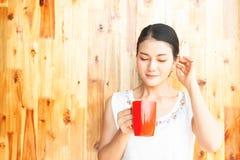 Νέα και όμορφη ασιατική γυναίκα που κρατά το κόκκινο φλυτζάνι ευτυχής υγιής στοκ εικόνες