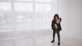 Νέα και όμορφη γυναίκα που κάνει την προθέρμανση στο στούντιο, προετοιμάζεται να χορεψει φιλμ μικρού μήκους