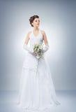 Νέα και όμορφη νύφη που στέκεται με την ανθοδέσμη λουλουδιών Στοκ Εικόνες