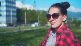 Νέα και όμορφη συνεδρίαση κοριτσιών σε έναν πάγκο σε ένα πάρκο οδών Το κορίτσι φορά ένα μαύρο και κόκκινο πουκάμισο και τα γυαλιά απόθεμα βίντεο
