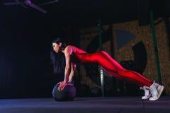 Νέα κατάλληλη γυναίκα που κάνει την ώθηση επάνω ή την άσκηση σανίδων στη σφαίρα ιατρικής στη γυμναστική στοκ εικόνες