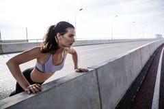 Νέα κατάλληλη γυναίκα που κάνει την ώθηση επάνω στη γέφυρα Στοκ Φωτογραφίες