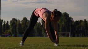 Νέα κατάλληλη γυναίκα που κάνει τις τεντώνοντας ασκήσεις στο πάρκο φιλμ μικρού μήκους