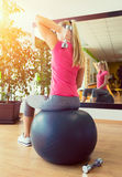 Νέα κατάρτιση γυναικών στη γυμναστική με τους αλτήρες μπροστά από έναν καθρέφτη Στοκ Εικόνες