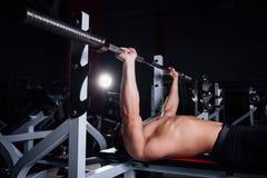 Νέα κατάρτιση bodybuilder στη γυμναστική, στήθος - barbell κλίνετε τον Τύπο πάγκων Στοκ Εικόνες