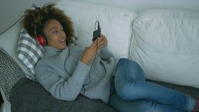 Νέα κατάψυξη γυναικών στον καναπέ με τις συσκευές απόθεμα βίντεο
