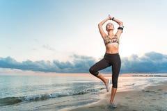 Νέα κατάλληλη γιόγκα άσκησης κοριτσιών στην παραλία στην ανατολή στοκ εικόνες