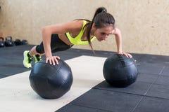 Νέα κατάλληλη γυναίκα που κάνει την ώθηση επάνω στη σφαίρα ιατρικής στη γυμναστική στοκ φωτογραφία