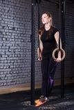 Νέα κατάλληλη γυναίκα sportwear να κάνει τράβηγμα-UPS στα γυμναστικά δαχτυλίδια ενάντια στο τουβλότοιχο στη διαγώνια κατάλληλη γυ Στοκ φωτογραφία με δικαίωμα ελεύθερης χρήσης