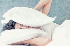 Νέα καυκάσια γυναίκα με τους μαύρους ύπνους τρίχας που καλύπτουν το κεφάλι και τα αυτιά της με τα μαξιλάρια Στοκ φωτογραφία με δικαίωμα ελεύθερης χρήσης