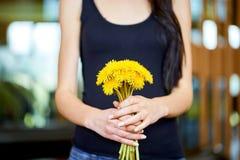 Νέα καυκάσια γυναίκα που κρατά μια δέσμη των πικραλίδων Στοκ φωτογραφία με δικαίωμα ελεύθερης χρήσης