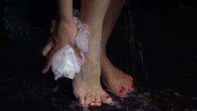 Νέα καυκάσια γυναίκα που παίρνει το ντους με το πήκτωμα και τον αφρό ντους Κλείστε επάνω την άποψη των ποδιών και των ποδιών απόθεμα βίντεο
