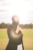 Νέα καυκάσια γυναίκα σε ένα πάρκο με να λάμψει ήλιων Στοκ φωτογραφία με δικαίωμα ελεύθερης χρήσης