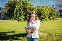 Νέα καυκάσια γυναίκα σπουδαστής με τα βιβλία στην πανεπιστημιούπολη Στοκ φωτογραφία με δικαίωμα ελεύθερης χρήσης