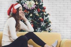 Νέα καυκάσια γυναίκα στην κόκκινη συνεδρίαση καπέλων στον καναπέ που ακούει τη MU στοκ εικόνες