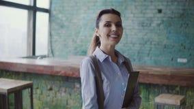 Νέα καυκάσια γυναίκα στο σύγχρονο coworking διάστημα Το πορτρέτο του όμορφου θηλυκού κρατά τα έγγραφα, δείχνει με το μολύβι απόθεμα βίντεο
