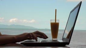 Νέα καυκάσια γυναίκα χρησιμοποιώντας το lap-top και πίνοντας το κούνημα φρούτων μάγκο με την άποψη θάλασσας Μακρινή εργασία και α φιλμ μικρού μήκους