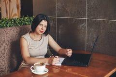 Νέα καυκάσια επιχειρηματίας με το lap-top και το σημειωματάριο Γυναίκα στον καφέ Στοκ Εικόνες