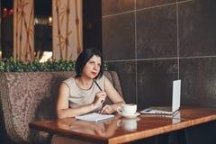 Νέα καυκάσια επιχειρηματίας με το lap-top και το σημειωματάριο Γυναίκα στον καφέ Στοκ εικόνα με δικαίωμα ελεύθερης χρήσης
