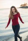Νέα καυκάσια λεπτή γυναίκα με τα ακατάστατα μακρυμάλλη φορώντας μαύρα τζιν και το κόκκινο πουκάμισο που περπατά τη θυελλώδη ημέρα Στοκ Εικόνες