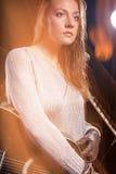 Νέα καυκάσια θηλυκή τοποθέτηση φορέων μουσικής με την κιθάρα ενάντια στο Μαύρο Συνδυασμός λάμψης και αλόγονου χρησιμοποιούμενων Στοκ φωτογραφία με δικαίωμα ελεύθερης χρήσης