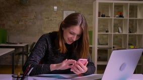 Νέα καυκάσια κοκκινομάλλης γυναίκα που κάνει σερφ το smartphone και τις αλλαγές οι συγκινήσεις από τη χαρά στο puzzlement στην αρ απόθεμα βίντεο
