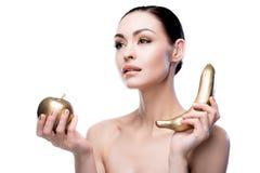Νέα καυκάσια κυρία που κρατά το χρυσές μήλο και την μπανάνα Στοκ εικόνα με δικαίωμα ελεύθερης χρήσης