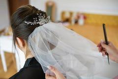 Νέα καυκάσια νύφη που παίρνει την τρίχα της γίνοντη για τη ημέρα γάμου της στοκ φωτογραφία
