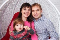 Νέα καυκάσια οικογένεια με τη μικρή κόρη καθμένος στο swin Στοκ Φωτογραφίες