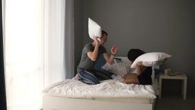 Νέα καυκάσια πάλη ζευγών με τα μαξιλάρια στο κρεβάτι με τα άσπρα φύλλα, γέλιο Πραγματική έννοια αγάπης ευτυχές πρωί απόθεμα βίντεο