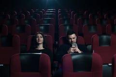 Νέα καυκάσια συνεδρίαση ζευγών στη κινηματογραφική αίθουσα Στοκ Φωτογραφία