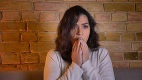 Νέα καυκάσια ταινία τρόμου προσοχής γυναικών brunette και κάλυψη του προσώπου της στο φόβο και της αμηχανίας στο άνετο σπίτι απόθεμα βίντεο