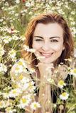 Νέα καυκάσια τοποθέτηση γυναικών brunette στο λιβάδι μαργαριτών, ομορφιά Στοκ Εικόνες