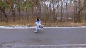 Νέα καυκάσια τρεξίματα φίλων κατά μήκος του δρόμου στο δάσος σε σε αργή κίνηση απόθεμα βίντεο