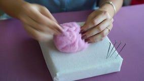 Νέα καυκάσια χέρια γυναικών κινηματογραφήσεων σε πρώτο πλάνο που κατασκευάζουν το μαλλί το ξηρό σεμινάριο πίλησης απόθεμα βίντεο