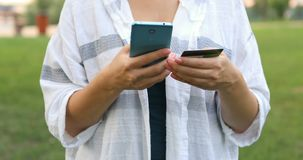 Νέα καυκάσια χέρια που αγοράζουν τα αγαθά από το Διαδίκτυο στο smartphone της με την πιστωτική κάρτα της φιλμ μικρού μήκους