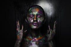 Νέα καλλιτεχνική γυναίκα στο μαύρο χρώμα και τη ζωηρόχρωμη σκόνη Καμμένος σκοτεινό makeup Δημιουργική τέχνη σωμάτων στο θέμα του  Στοκ Φωτογραφία