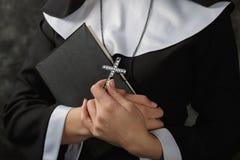Νέα καλόγρια σε μια Βίβλο εκμετάλλευσης τηβέννων και σταυρός ενάντια στο σκοτεινό τοίχο Κινηματογράφηση σε πρώτο πλάνο Γυναίκα πο στοκ εικόνα