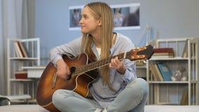 Νέα κιθάρα γυναικείου παιχνιδιού στο δωμάτιό της, τραγούδι γραψίματος, που ονειρεύεται τη σταδιοδρομία μουσικής απόθεμα βίντεο
