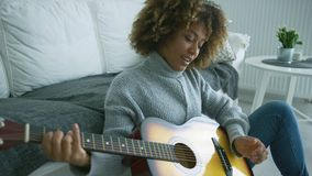 Νέα κιθάρα παιχνιδιού γυναικών στο σπίτι απόθεμα βίντεο