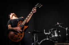 Νέα κιθάρα παιχνιδιού γυναικών κατά τη διάρκεια στοκ φωτογραφία