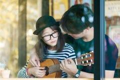 Νέα κιθάρα παιχνιδιού ζευγών αγάπης μαζί στον καφέ στοκ εικόνες