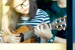 Νέα κιθάρα παιχνιδιού ζευγών αγάπης μαζί στον καφέ στοκ φωτογραφία με δικαίωμα ελεύθερης χρήσης