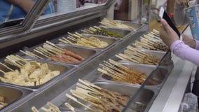 Νέα κινεζικά κορίτσια που παίρνουν το γρήγορο φαγητό σε ένα ραβδί απόθεμα βίντεο